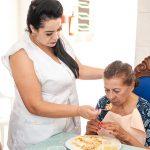 Cuidadora alimentando idosa