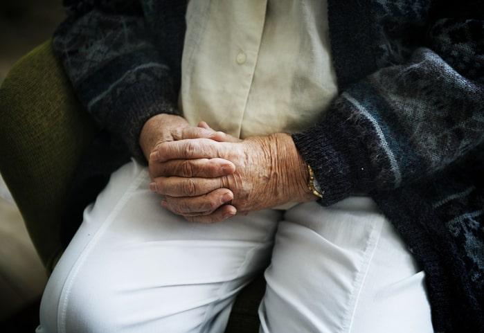 Idoso sentado de mãos cruzadas