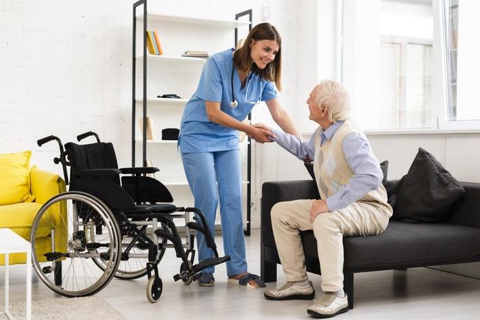 Idoso contando com o auxílio de enfermeira
